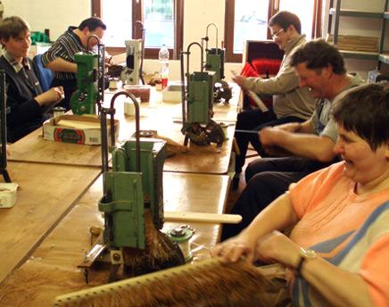 Innenansicht der Blindenwerkstatt in Dresden. Männer und Frauen arbeiten an Werkbänken.
